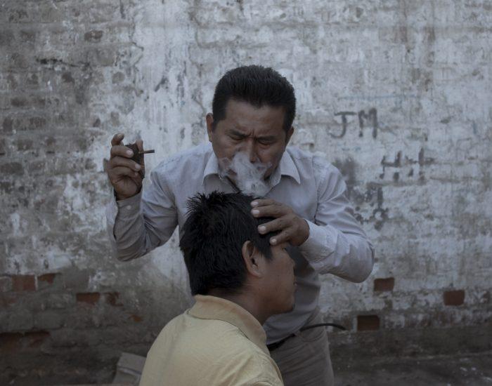 Pablo Faustino Díaz trata a un paciente de la comunidad de Cantagallo, en Lima, con humo de tabaco. Pablo es enfermero del Estado y experto en medicina tradicional shipibo-konibo; por eso utiliza esencias de plantas, así como humo y vaporizaciones, como método paliativo ante la amenaza del virus. En Cantagallo logró unir sus saberes de enfermero y de curandero indígena para proteger a su comunidad, en donde, según el Ministerio de Salud peruano, el 98 % de la población se vio afectada por el virus.