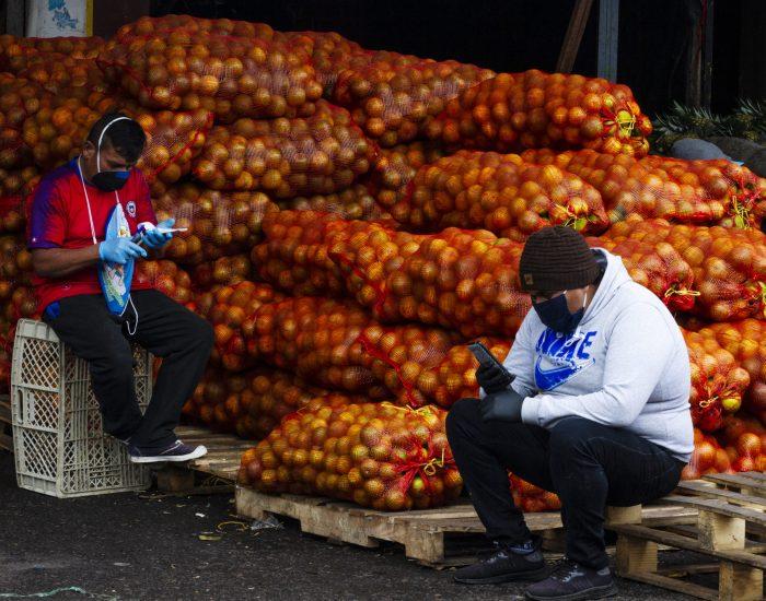 Dos vendedores de naranjas esperan el siguiente cargamento en el Mercado Mayorista de Quito.